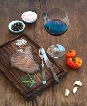 Cooked meat t-bone steak on serving board with garlic cloves, tomatoes, rosemary, spices and glass of red wine over rustic wooden .