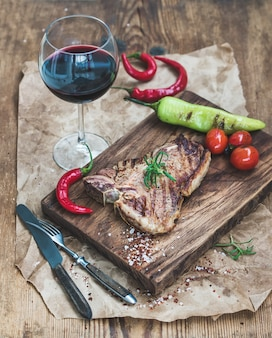 Cooked meat t-bone steak on serving board with roasted tomatoes, chili peppers, fresh rosemary, spices and glass of red wine over rustic wooden