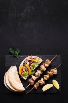 Carne cotta e kebab di verdure sulla tavola nera