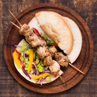 Cooked meat and veggies kebab on skewers with pita