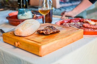 Cooked meat with dough on wooden chopping board