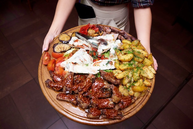 Cooked meat with vegetables on a large wooden board in the hands of the waiter.