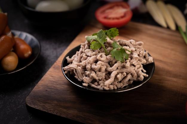 黒いプレートにミントの葉、木製のまな板にトマトを添えて調理した豚挽き肉