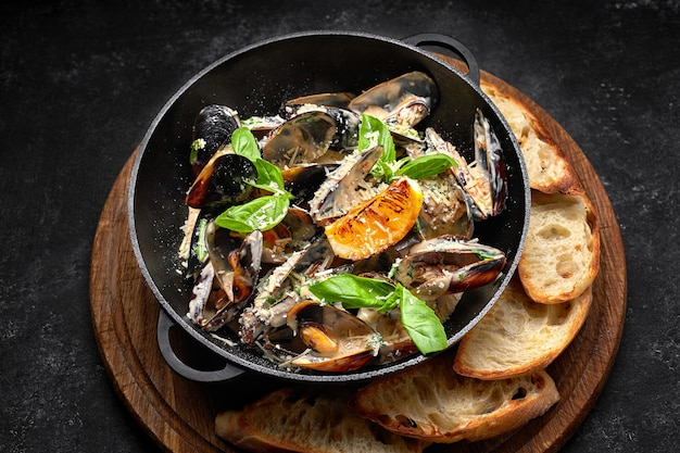 Cooked mussels in a skillet with cheese and basil leaves, on a wooden board, on a dark table