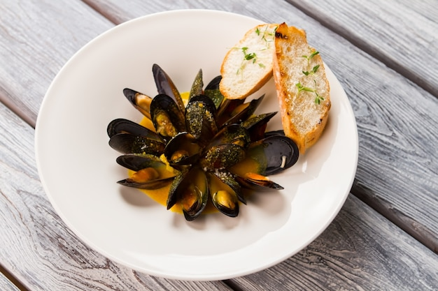 Cooked mussels with sauce. sliced baguette on white plate. freshly cooked food on table. simple recipe of boiled mussels.