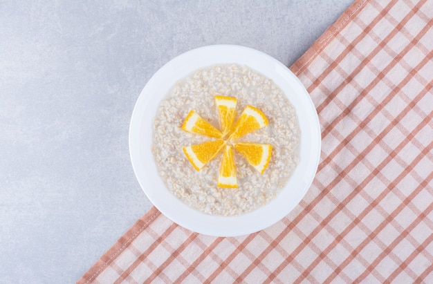 Cooked oatmeal topped with orange slices on marble surface