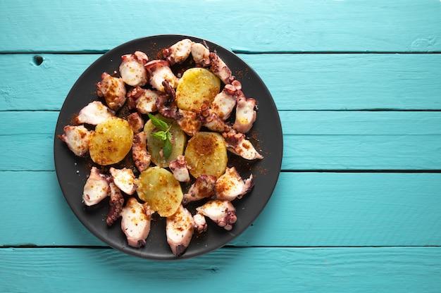 Приготовленное блюдо из осьминога подается с нарезанным отварным картофелем, копченой паприкой и оливковым маслом. на синей деревянной поверхности, вид сверху