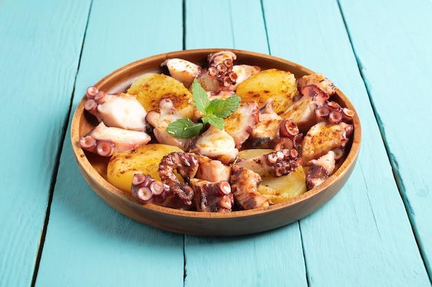 Приготовленное блюдо из осьминога подается с нарезанным отварным картофелем, копченой паприкой и оливковым маслом. на синей деревянной поверхности