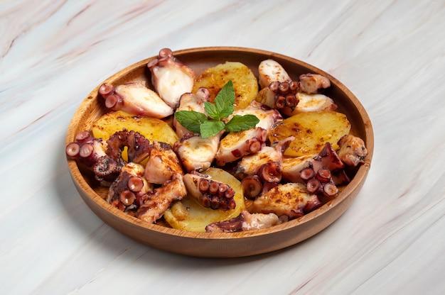 Приготовленное блюдо из осьминога подается с нарезанным отварным картофелем, копченой паприкой и оливковым маслом. на мраморной поверхности