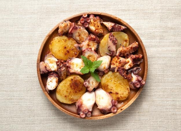 Приготовленное блюдо из осьминога подается с нарезанным отварным картофелем, копченой паприкой и оливковым маслом. вид сверху
