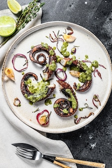 Приготовленные щупальца осьминога с соусом песто, тимьяном и луком