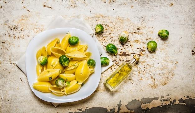 オリーブオイルを入れた白い皿に芽キャベツを入れて調理したパスタ。素朴な背景に。上面図
