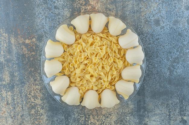 Приготовленная трубка и сырые пасты с галстуком-бабочкой в миске на мраморной поверхности.