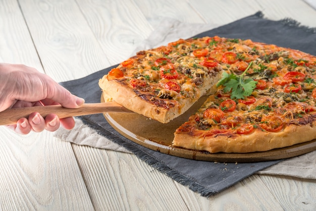 Cooked pizza on a wooden wall with cut slice