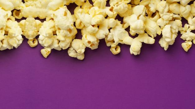 Приготовленный попкорн на фиолетовом фоне с копией пространства