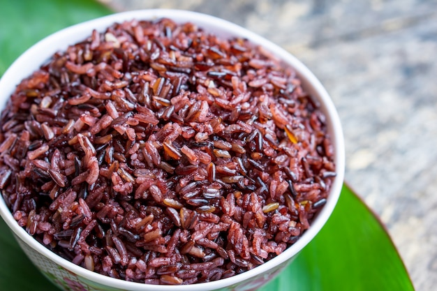 Cooked purple rice berry in bowl over green leaf