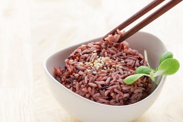 Приготовленная ягода пурпурного риса в белой миске с ростками подсолнечника и палочками для еды.