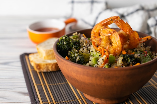 Cooked quinoa with fresh vegetables and fried shrimps in a bowl