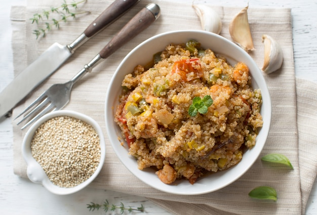 Cooked quinoa with vegetables and shrimps in bowl