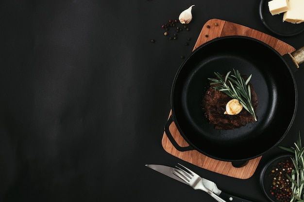Cooked ribeye steak on cast-iron pan and board, rosemary, knife, fork, butter