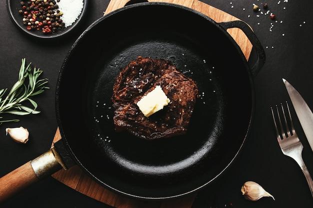 Cooked ribeye steak on pan, pepper, rosemary, salt, garlic, knife, fork, butter
