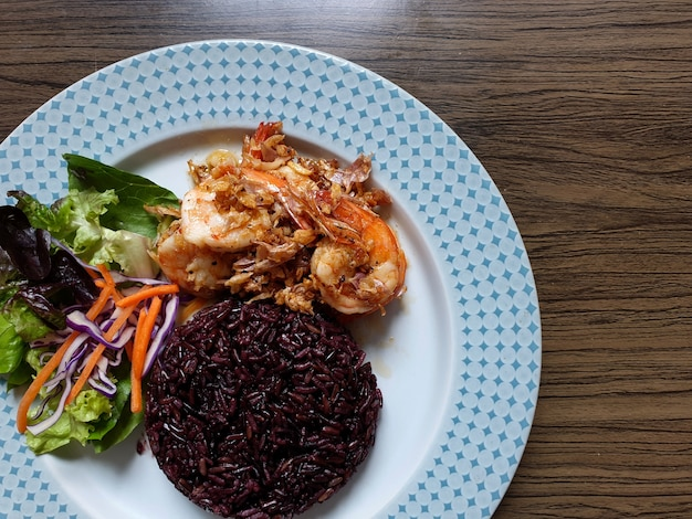 Cooked rice berry and fried shrimp with garlic and pepper mixed salad in a plate