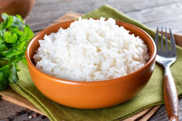 Приготовленный рис в миске на старом деревянном столе