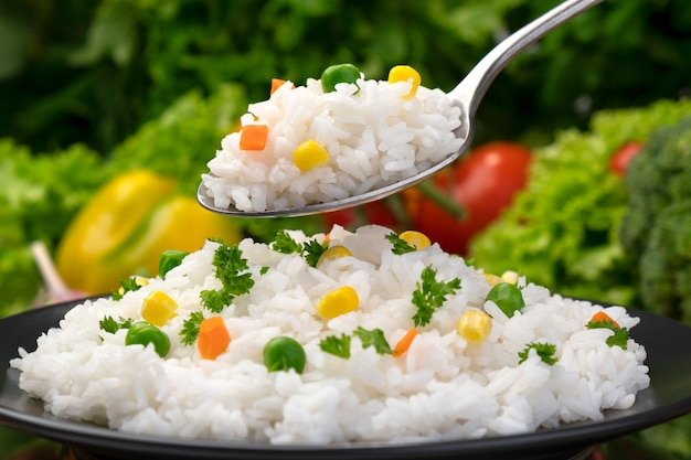 Cooked rice porridge on spoon, served with herbs and vegetables on black plate