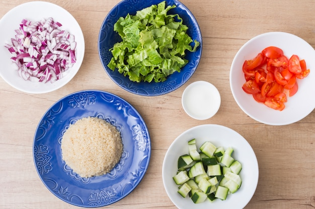 Cooked rice with cut vegetables in bowls