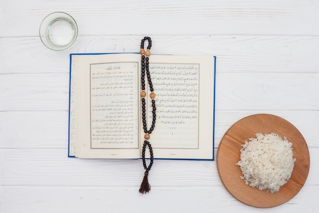 Cooked rice with quran and beads on light table