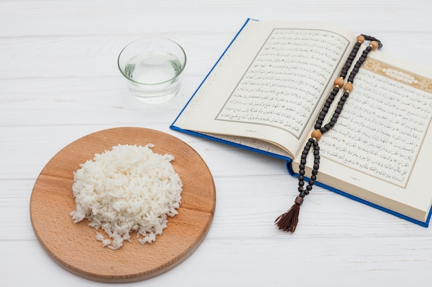 Cooked rice with quran and beads on table
