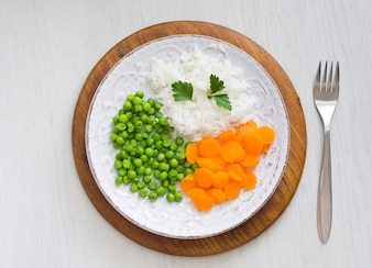 Cooked rice with vegetables and parsley on plate on wooden board