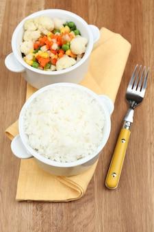 Приготовленный рис с овощами на деревянном столе