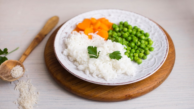 Cooked rice with vegetables on wooden board near spoon