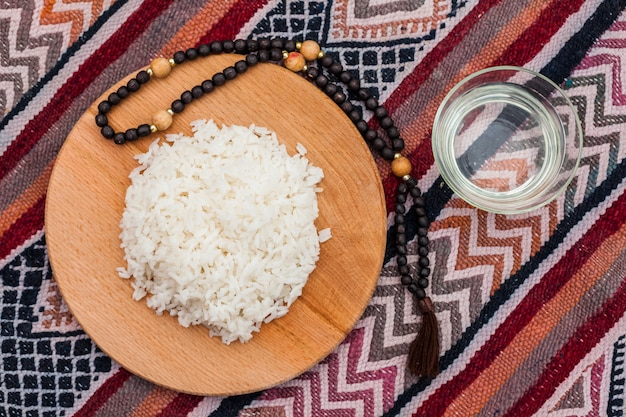 Cooked rice on wooden board with beads