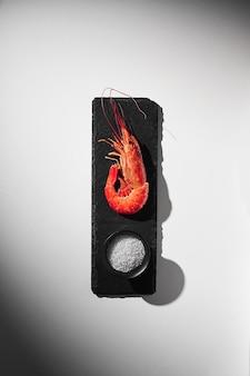 Cooked royal prawn on slate board with coarse sea salt