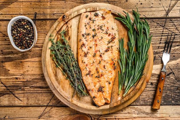 Приготовленное филе лосося с зеленью и розовым перцем. деревянный фон. вид сверху.