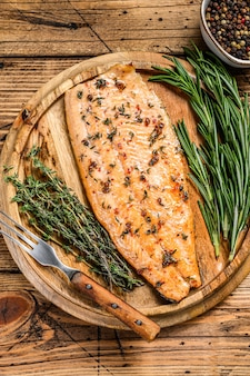 Приготовленное филе лосося с зеленью и розовым перцем. деревянный стол. вид сверху.