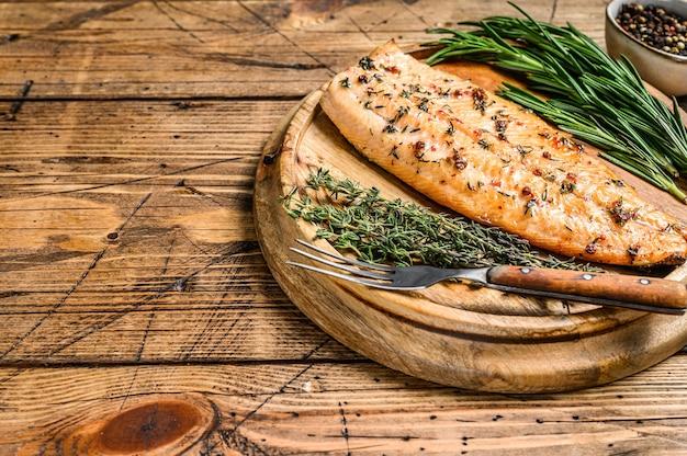 Приготовленное филе лосося с зеленью и розовым перцем
