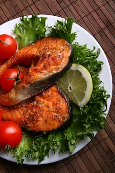 Cooked salmon steak , herbs, lemon, garlic, olive oil and tomato