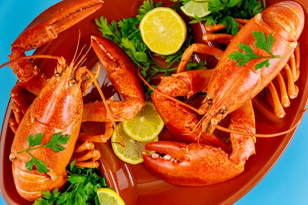 Cooked sea large lobster with lemon on tray.
