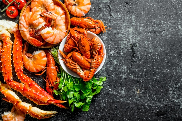 Cooked shrimp, crayfish and crab with parsley. on dark rustic