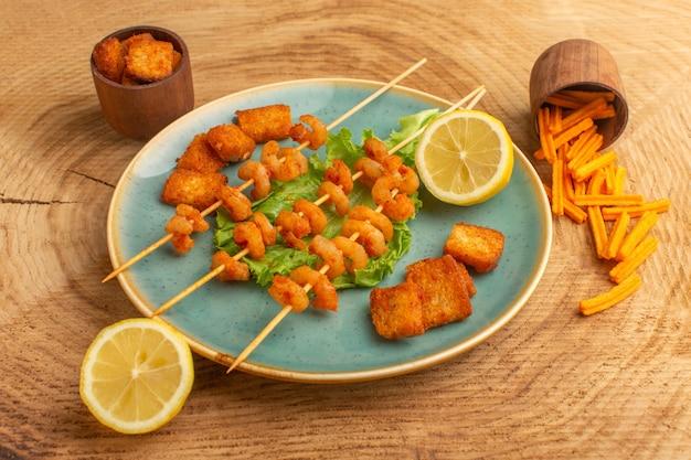 Приготовленные креветки на палочках внутри синей тарелки с зеленым салатом и дольками лимона на деревянном столе