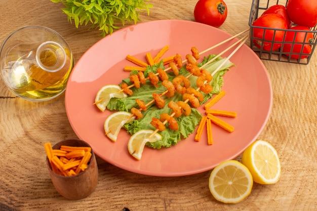 Приготовленные креветки на палочках внутри персиковой тарелки с ломтиками лимона масло зеленого салата на деревянном столе