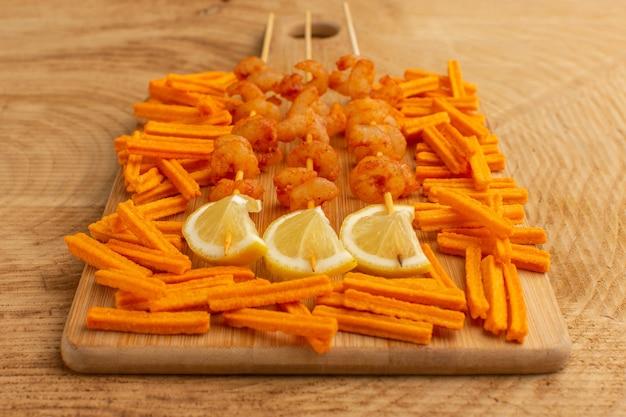 Приготовленные креветки на палочках с дольками лимона и сухариками на деревянном столе