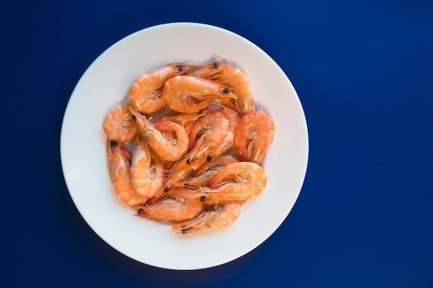 Вареные креветки, жареные или вареные морепродукты, королевские тигровые креветки с зеленью, специи на белой тарелке. вид сверху. здоровая пища. безуглеводная кетопротеиновая диета для похудения