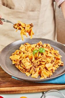 デジタルタッチパッドレシピを使用したオンライン学習から調理されたスパゲッティボロネーゼは、完成した料理を味わう