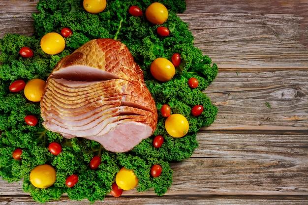 신선한 레몬, 케일, 토마토와 함께 조리 된 나선형 슬라이스 히코리 훈제 햄. 휴일 식사.