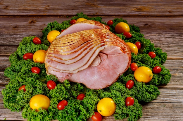 Cooked spiral sliced hickory smoked ham with fresh lemon and tomatoes. holiday meal.