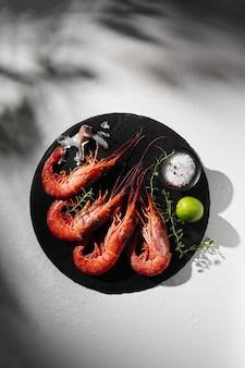 Приготовленные тигровые креветки с приправами и лаймом на круглой шиферной доске
